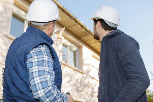 Naklejka architect and mason inspecting the exterior of the house