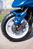 Front wheel of blue modern scooter on the gravel road - 215490843