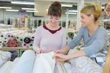 smiling brunette choosing fabric skeins in textile shop