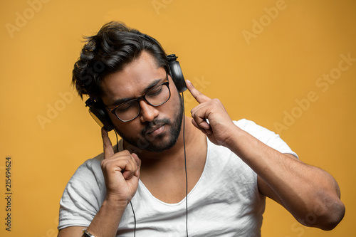 close up portrait of good-looking Indian model enjoying listening to the music. listen to favourite band
