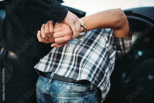 Leinwanddruck Bild Policeman arrests the car thief on road
