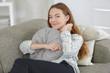 Young lady on sofa cuddling cushion