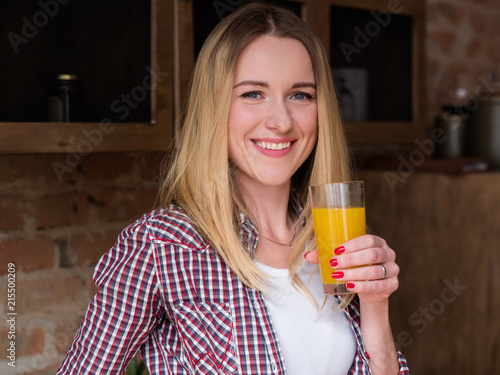 wellness diet drink. natural delicious organic orange juice. smiling healthy young woman holding a glass of fresh beverage