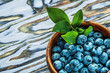 Quadro Bilberries green leaves in wooden bowl on wood board