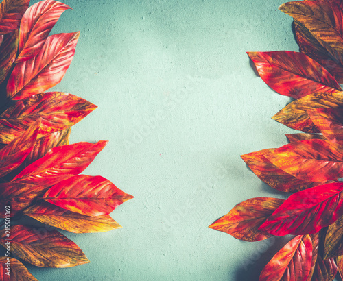 Bright orange red autumn leaves frame on sunny turquoise background, top view with copy space. Fall pattern layout. Retro styled