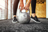 girl lifting kettlebell from the floor in the gym
