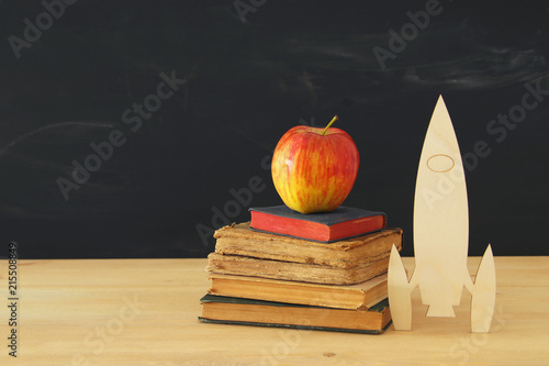Back to school concept. wooden rocketand pencils next to books in front of classroom blackboard.