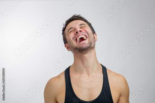 Foto Murales young man is laughing with pleasure. angry laugh. personal trainer is laughing at his students