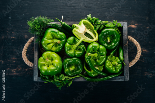 Foto Murales Fresh green pepper in a wooden box. Organic food. Top view. Free space for text.