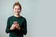 Leinwanddruck Bild - Portrait of a smiling pretty casual woman holding smartphone over grey background