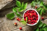Fresh sweet raspberries in a ceramic bowl on a wooden table. The concept of nutrition health or detoxification. Copy space, top view flat lay background.