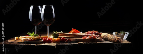 Italian antipasti wine snacks set. Cheese variety, Mediterranean olives, crudo, Prosciutto di Parma, salami and wine in glasses over wooden grunge background. - 215525217