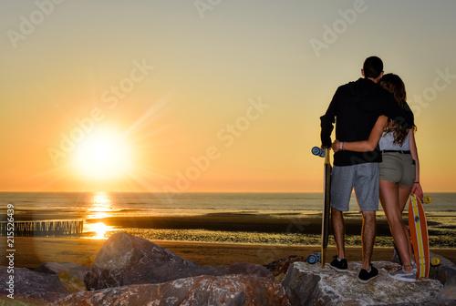 jeune couple face au soleil couchant