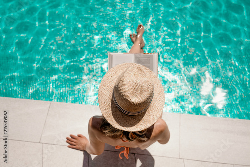 Frau am Pool liest Buch - 215539062
