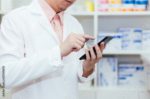 Foto Spatwand Apotheek Pharmacist, Physician using a mobile phone at drugstore room. Doctor touching a cell phone in medical concept.