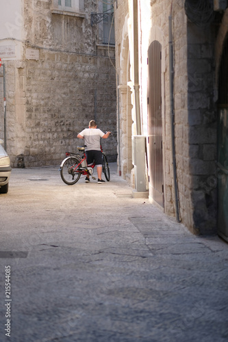 Aluminium Smalle straatjes A boy with a bicycle on a narrow street of an ancient city. Italy