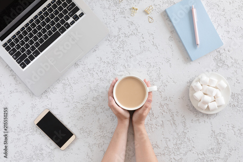 Nowoczesne i modne biurko z laptopem, niebieskim notatnikiem, telefonem komórkowym, długopisem, piankami i filiżanką kawy, płaskie leżało. Odgórny widok kobieta stół z kopii przestrzenią