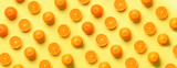 Fruit pattern of fresh orange slices on yellow background. Top view. Copy Space. Pop art design, creative summer concept. Half of citrus in minimal flat lay style. Banner.