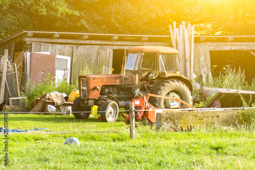 Canvas Zwavel geel Agriculture, an old broken tractor stands on a farm illuminated by the sun