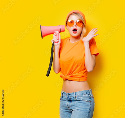 Leinwandbild Motiv Young style girl in orange clothes with pink megaphone on yellow background. Symbolizes female resistance. Clothes in 1980s style