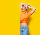 Young style girl with orange glasses and headphones on yellow background. Clothes in 1980s style - 215559665