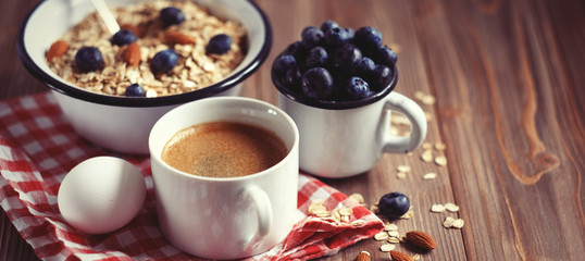 A healthy breakfast is a great start to a new day. Oatmeal porridge, coffee, berries and nuts on a wooden table. © Raisa Kanareva