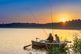 father and son catch fish from a boat at sunset - 215565408
