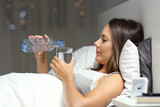 Woman drinking water on the bed in the night
