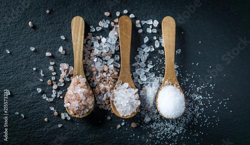 Leinwandbild Motiv Different types of salt. Top view on three wooden spoons