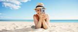 happy woman taking photo with retro photo camera on seacoast - 215573496