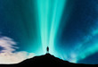 Leinwandbild Motiv Aurora borealis and silhouette of standing man on the mountain. Aurora and traveller. Starry sky and green polar lights. Night landscape with northern lights and people. Concept. Nature background