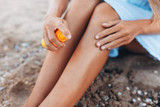 Beautiful girl, sun cream application, on the beach, feet close-up, jar of sun cream, isolated - 215583677