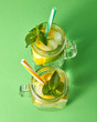 Leinwanddruck Bild - Citrus fruits slices of lemon and lime, ice, water and plastic straws in the glass on a green background. Two glass jars with a cold natural handmade lemonade with bubbles of air. Top view.