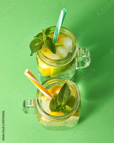Leinwandbild Motiv Citrus fruits slices of lemon and lime, ice, water and plastic straws in the glass on a green background. Two glass jars with a cold natural handmade lemonade with bubbles of air. Top view.
