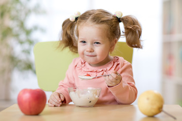 kid girl eating healthy food at home or daycare
