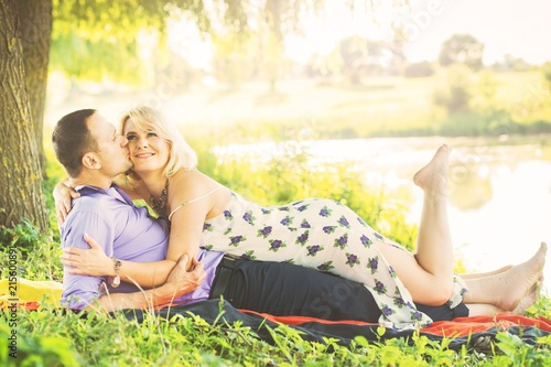 Leinwanddruck Bild beautiful couple spends time romantically on the river bank at sunset in warm summer weather. the embrace of a man and a woman. I love