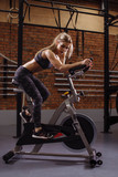 young awesome pleasant fitness girl testing her new stationary bicycle . side view photo