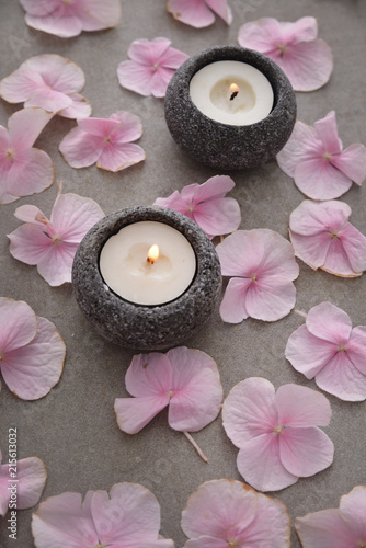 Plexiglas Spa Many Pink hydrangea petals with two candle in stone bowl on gray background