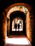 Picturesque medieval narrow street of San Gimignano old town with two person silhouette in the shadow, Tuscany, Italy.