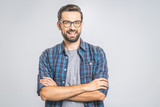 Happy young man. Portrait of handsome young man in casual shirt keeping arms crossed and smiling while standing against grey background - 215634201