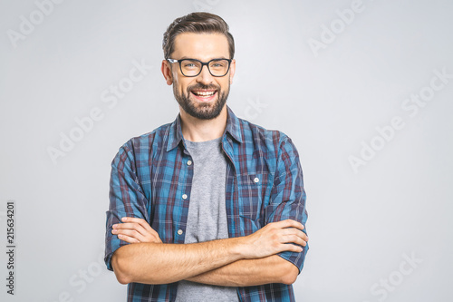 Foto Murales Happy young man. Portrait of handsome young man in casual shirt keeping arms crossed and smiling while standing against grey background
