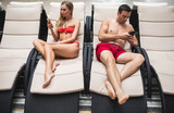 Web addiction. Full length of couple lying on deck chairs and using mobile. They are turned backs from each other while surfing net