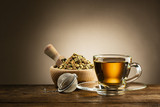 glass cup of tea with infuser and herbal tea on wooden table