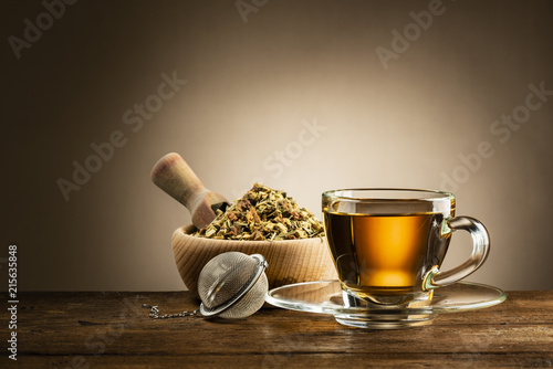 Fototapeta glass cup of tea with infuser and herbal tea on wooden table