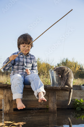 Foto Murales Happy boy go fishing on the river, one children fisherman with a fishing rod on the shore of lake