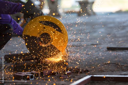Leinwandbild Motiv worker wear safety glove and use cutting machine to cut steel