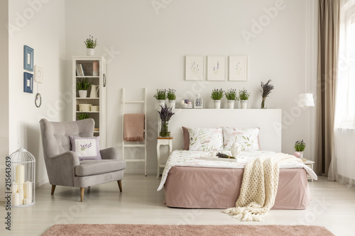 Real photo of a feminine bedroom interior with a comfy armchair, bed, plants and shelf © Photographee.eu