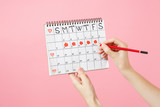 Close up female holds in hand red pencil, female periods calendar for checking menstruation days isolated on trending pink background. Medical healthcare gynecological concept. Copy space. Advertising - 215647607