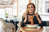 Sensual woman rolling spaghetti and keeping on a fork to eat