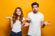 Leinwanddruck Bild - Image of happy young people man and woman in basic clothing throwing up arms with puzzlement, isolated over yellow background